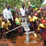 Local people investigate their new, 140-ft deep well which will bring them clean water.